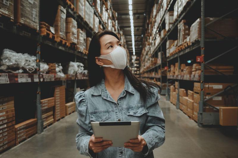 Woman wearing mask examining warehouse
