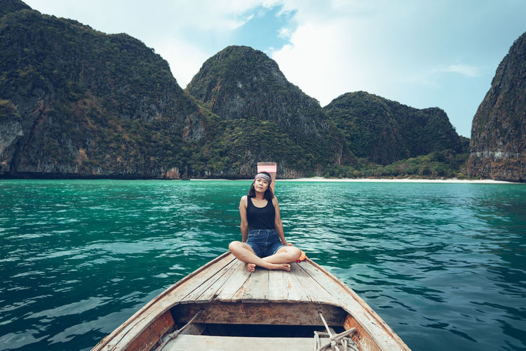 Full length of woman sitting on boat in sea against mountains