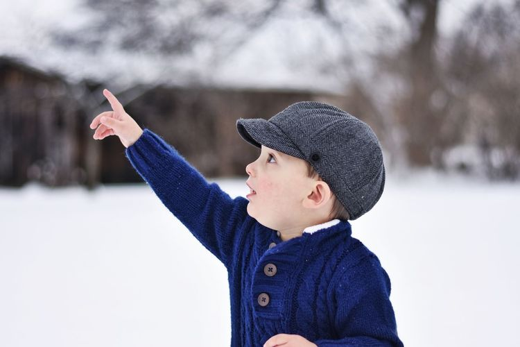 Close-Up Of Cute Boy Pointing Outdoors During Winter