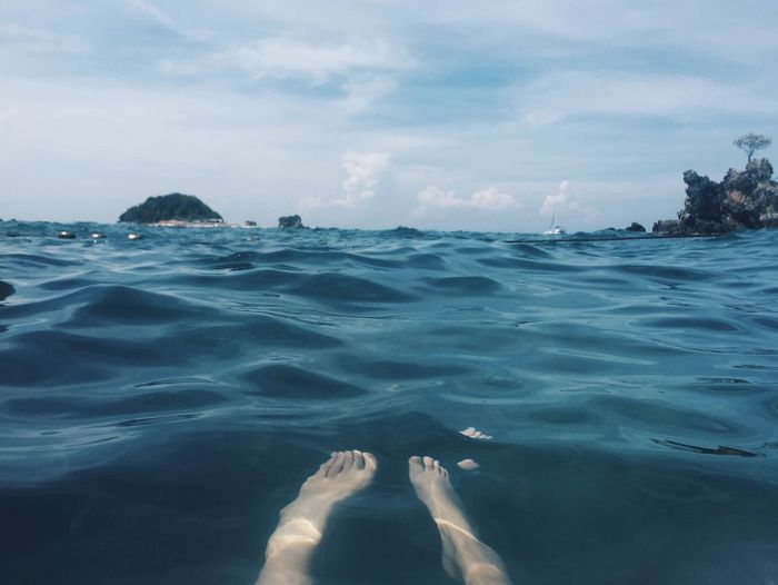 Low Section Of Person Swimming In Sea Against Sky