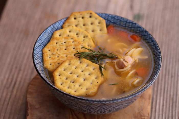 Chicken noodle soup in a blue and white bowl with crackers, all sitting on a wood cutting board. Broth Chicken Chicken Noodle Soup Chicken Soup Close-up Comfort Food Crackers Day Food Food And Drink Freshness Healthy Eating No People Soup Table Wood
