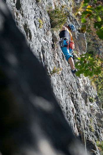 An athlete is climbing, high in the rocks throught the sky and the nature in the Jonte Canyon in the region of Lozère in the South of France. Adventure Cliff Climbing Day Extreme Sports Headwear Healthy Lifestyle Leisure Activity Lifestyles Low Angle View Mountain One Person Real People RISK Rock - Object Rock Climbing Rock Face Rope Skill  Sport Sports Helmet Strength Women Young Adult Young Women Go Higher