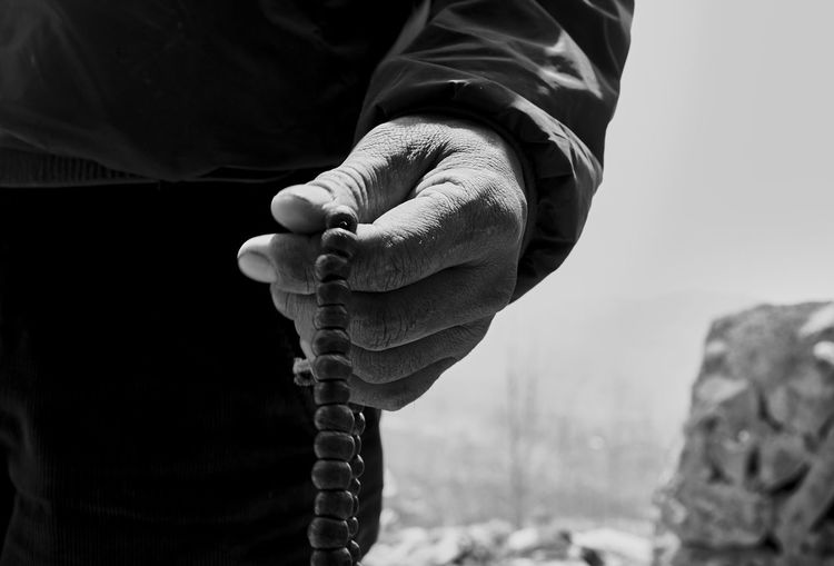 Midsection of man holding prayer beads