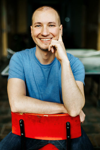 Happily smiling caucasian man in blue shirt sitting on a red chair Smiling Happiness Looking At Camera Front View Portrait Sitting Emotion Real People Casual Clothing Young Adult Toothy Smile Teeth Seat Focus On Foreground Indoors  Leisure Activity Lifestyles Blue Shirt Smart Clever Joyful Confident  Student Student Life Man