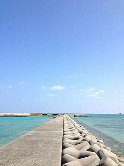Walkway By Tetrapods Amidst Sea Against Blue Sky