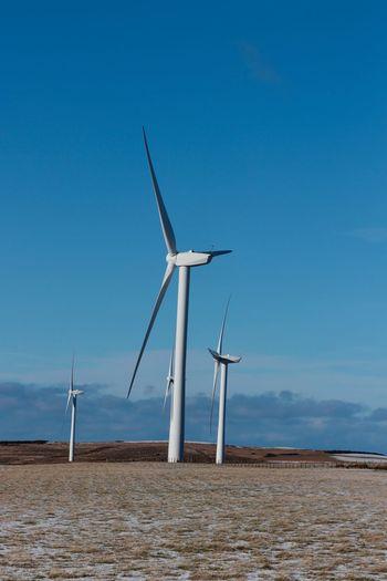 Windmill on wind turbines against blue sky
