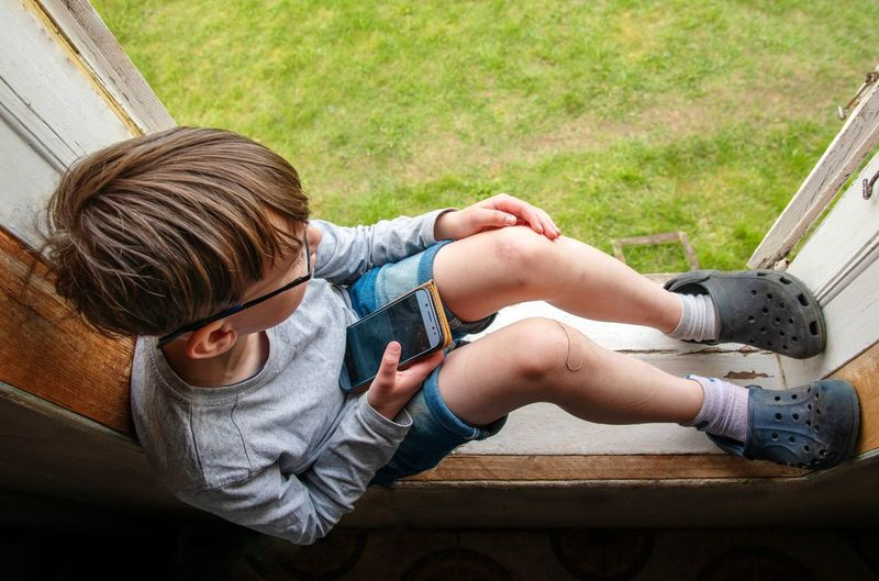 High angle view of boy sitting on window sill