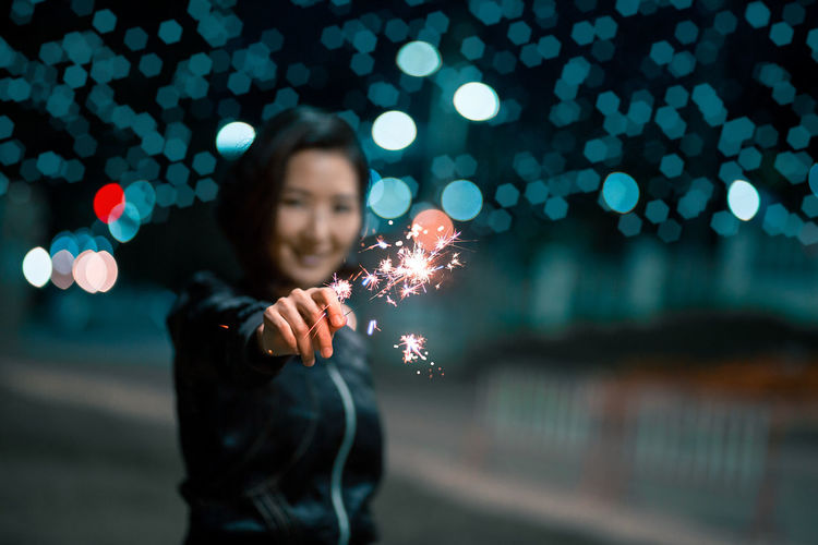 Smiling woman holding lit sparkler at night