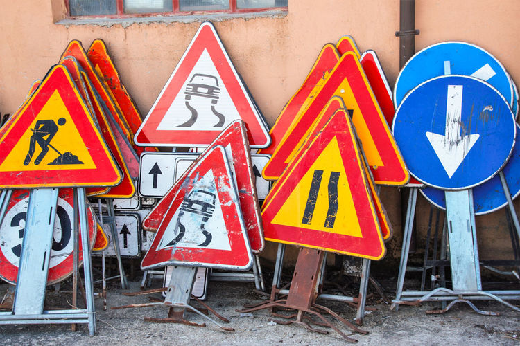 Architecture Arrow Symbol Blue Communication Day Design Guidance Human Representation Information Information Sign Male Likeness No People Outdoors Representation Road Road Sign Shape Sign Triangle Shape Warning Sign