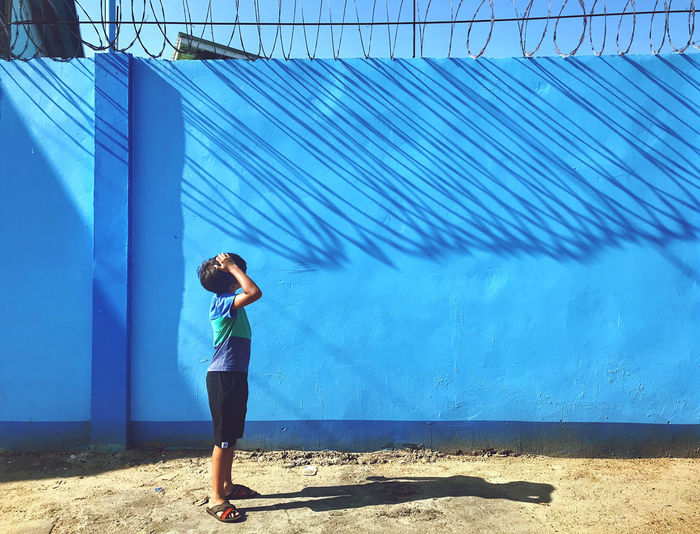 Full length of woman standing against blue sky