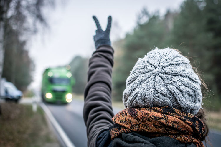 Focus On Foreground Transportation One Person Rear View Winter Mode Of Transportation Knit Hat Hat Clothing Day Headshot Travel Real People Car Nature Motor Vehicle Portrait Cold Temperature Tree Warm Clothing Outdoors Hood - Clothing Arms Raised Human Arm Vigil