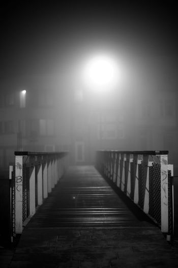 Empty footpath by illuminated street against sky during foggy weather