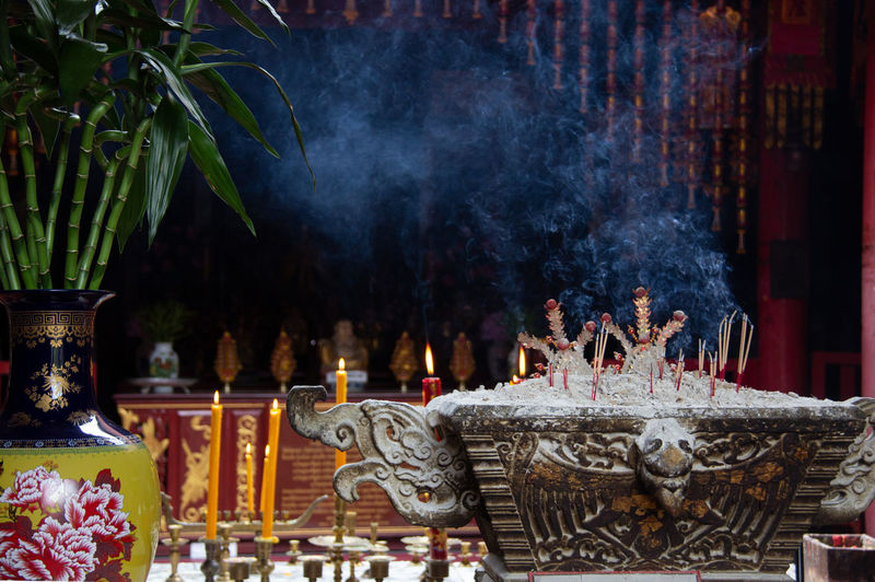 Candles and incense sticks burning against temple
