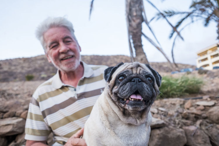 senior man with grey hair smiling with pug carlino dog Pug Carlino Animal Themes Attention Please Bonding Carlino Cane Dog Casual Clothing Day Dog Domestic Animals Friendship Happiness Leisure Activity Lifestyles Looking At Camera Nature One Animal One Person Outdoors Pets Portrait Real People Senior Adult Sitting Smiling