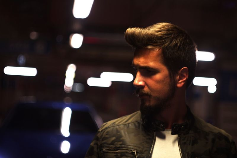 Young man wearing jacket looking away in illuminated parking lot