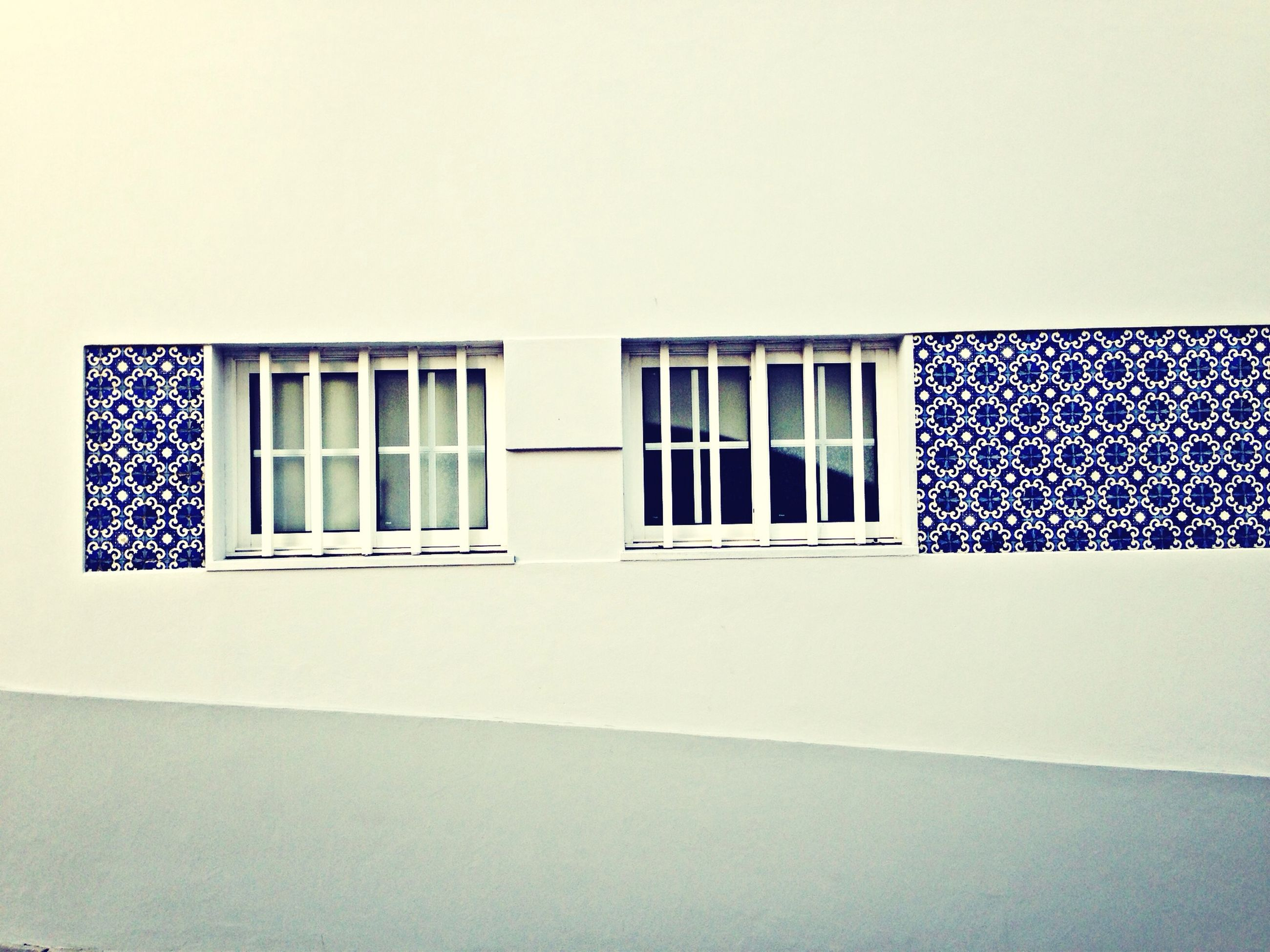 window, architecture, built structure, copy space, building exterior, clear sky, indoors, wall, glass - material, wall - building feature, blue, pattern, house, no people, design, geometric shape, building, day, closed, in a row