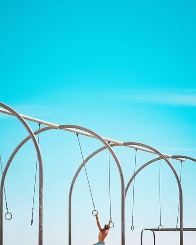Low angle view of woman hand against blue sky