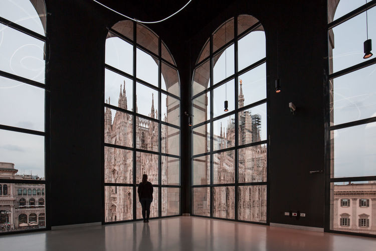 Woman looking at milan cathedral through glass window