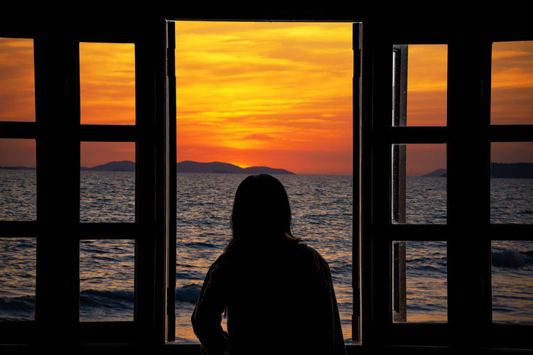 Rear view of silhouette woman looking at sea against sky during sunset