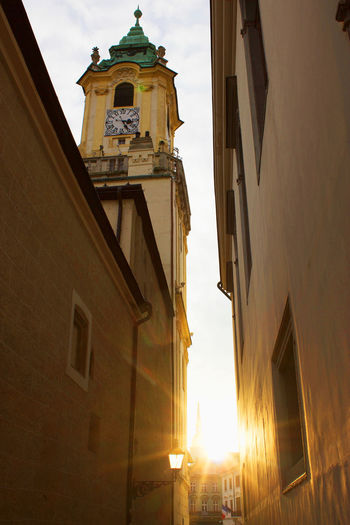 Sun Drenched Alleyway Faith Pozsony Alleyway Architecture Bell Tower Bratislava Building Exterior Built Structure Central Europe Central European Cross Day Glaring Low Angle View No People Outdoors Place Of Worship Religion Sky Spirituality Steeple Sun Drenched Sunlight Sunrise Sunset