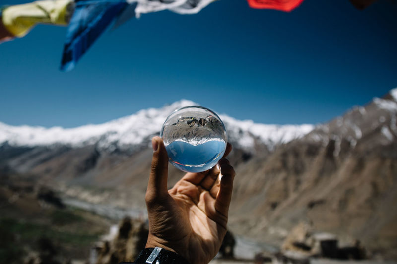 Cropped hand of man holding crystal ball against snowcapped mountain