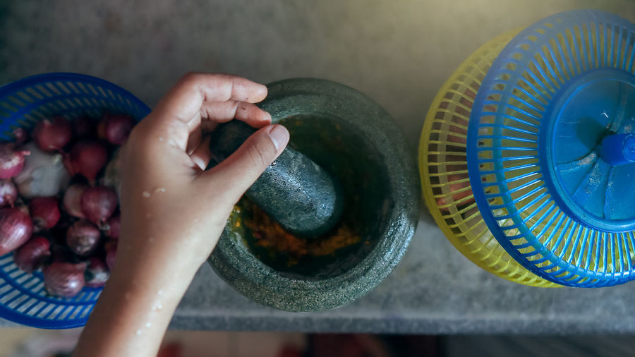 A mortar and pestle or lesung batu in malay with onion and chillies / spices. cooking concept.