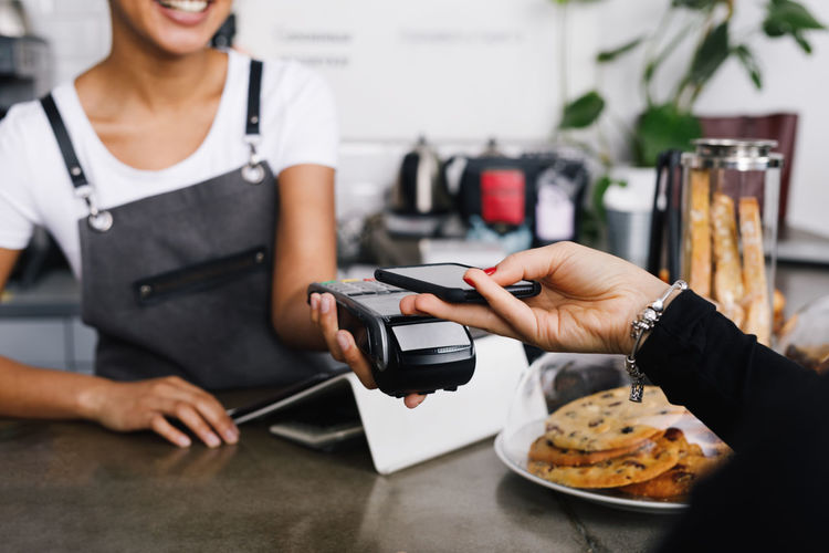 Cropped Hand Of Customer Using Mobile Phone For Contactless Payment To Owner At Cafe