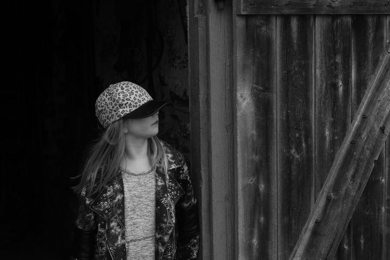 Girl wearing cap looking away while standing by wooden wall