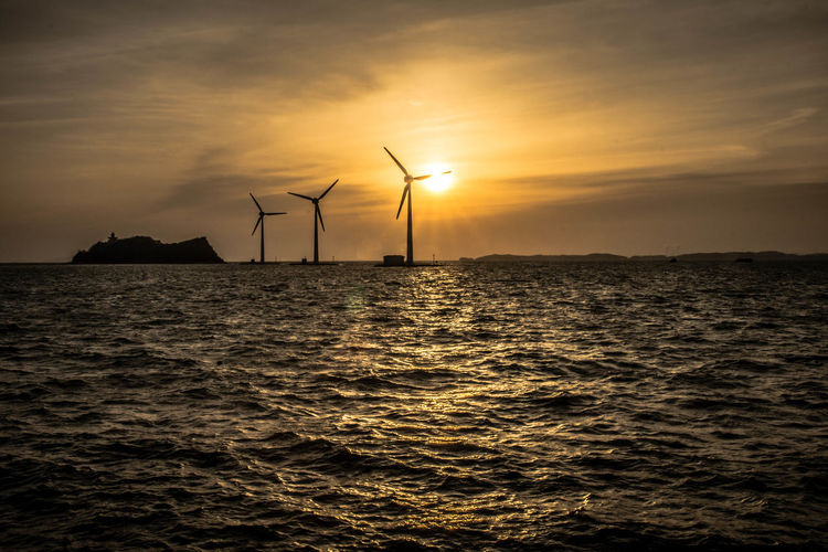 Silhouette of wind turbines on sea at sunset