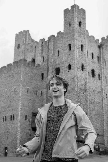 Low angle view of smiling man against historic building