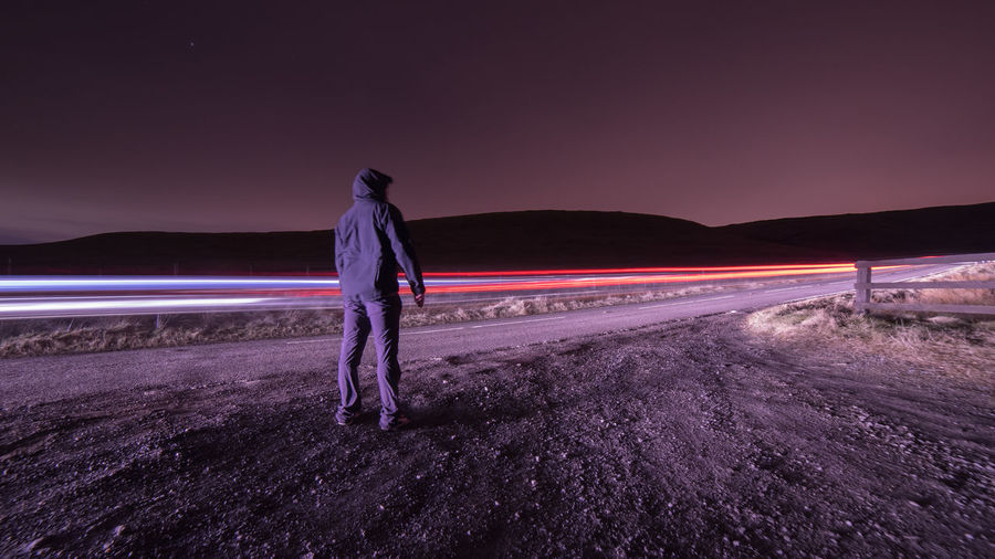Sky Night Illuminated One Person Long Exposure Standing Nature Full Length Motion Scenics - Nature Light Trail Land Beauty In Nature Sunset Rear View Real People Road Men Casual Clothing Purple