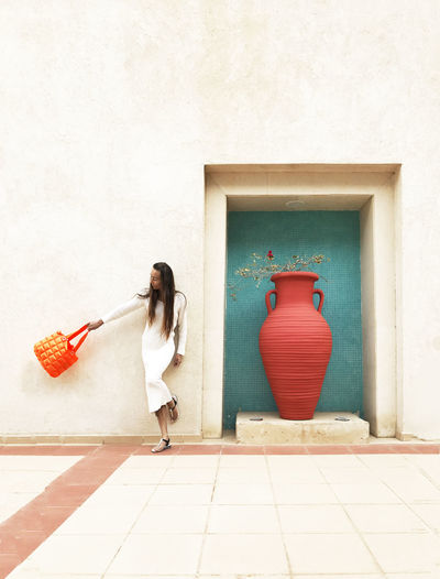 Woman holding purse standing by huge vase against wall