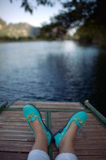 Low section of woman relaxing on pier over lake