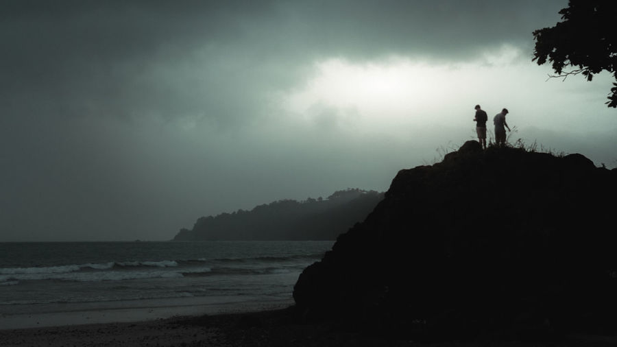 Silhouette people standing on cliff by sea against sky