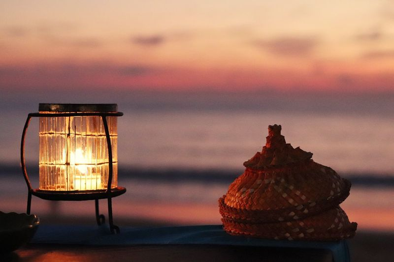 Close-up of illuminated lamp on table against sea during sunset
