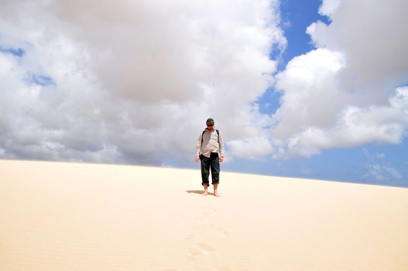 Full length of woman standing against cloudy sky