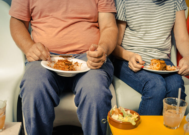 Mid section of couple eating food