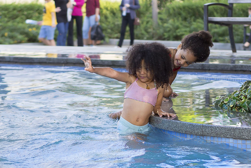 Water Child Girls Childhood Women Females Real People Family Leisure Activity Togetherness Day Lifestyles Waterfront Bonding People Men Two People Three Quarter Length Swimming Pool Daughter Positive Emotion Sister Outdoors Innocence