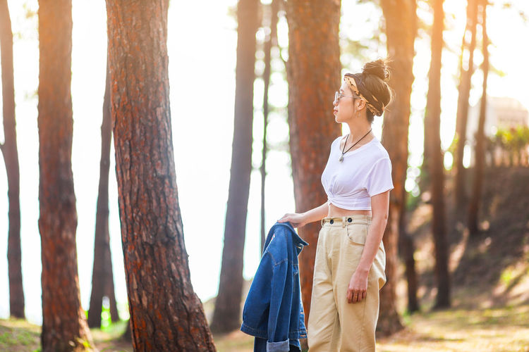 Tree Trunk Tree Trunk Plant Casual Clothing Women Nature Adult Standing Leisure Activity Three Quarter Length Land Forest One Person Lifestyles Day Front View Focus On Foreground Young Adult Outdoors Hairstyle WoodLand Beautiful Woman