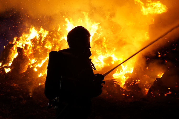 Silhouette firefighter against fire at night