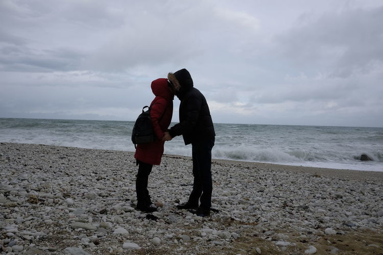 Couple Kissing While Standing On Shore At Beach Against Sky