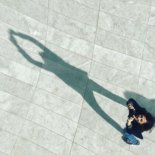 Directly Above Shot Of Smiling Woman Taking Selfie By Shadow On Footpath