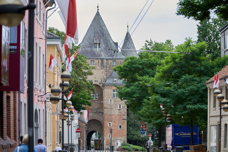 NEUSS, GERMANY - AUGUST 08, 2016: Pedestrants walk towards the historic town gate Advertising Business Finance And Industry City Life City Street Commercial Dock Culture Downtown Historic Historic Buildings Urban History Medieval Neuss, Germany Pedestrants Shopping