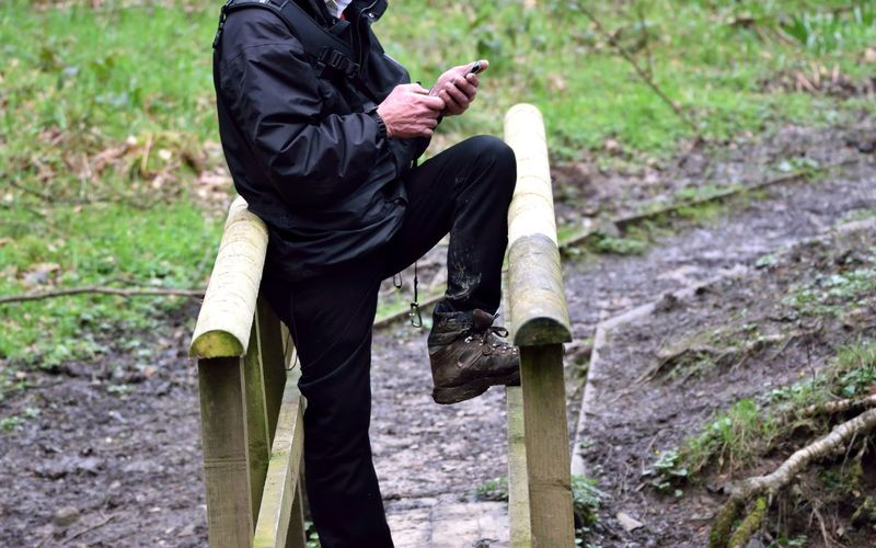 Low Section Of Man Using Mobile Phone While Leaning On Railing