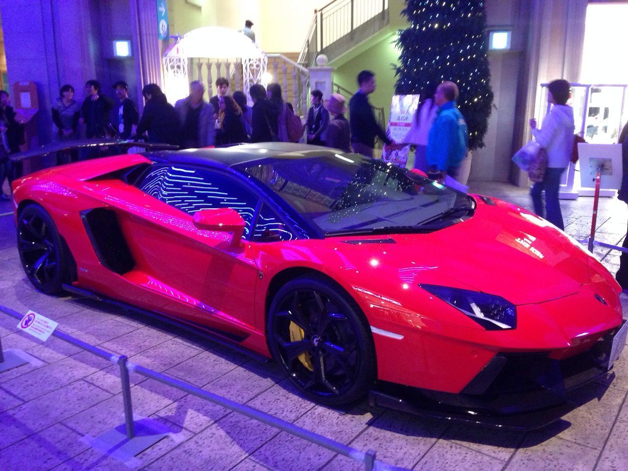 car, red, men, luxury, real people, transportation, women, architecture, land vehicle, large group of people, night, standing, illuminated, outdoors, building exterior, people