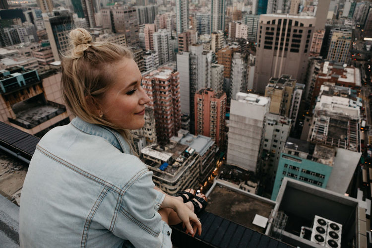 Woman sitting on building terrace in city