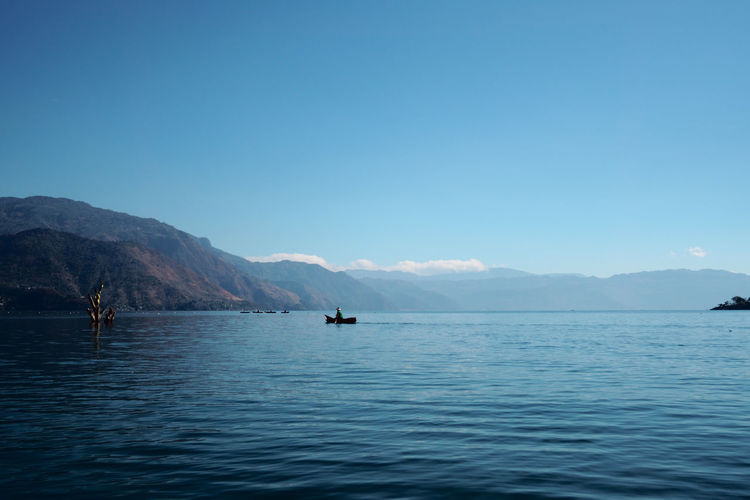 Out on the lake Astrology Sign Atitlan Lake Beauty In Nature Blue Boat Clear Sky Day Fisherman Lake Landscape Mountain Nature Nautical Vessel No People Outdoors Peaceful Quiet Rippled Scenics Sea Sky Tranquil Scene Travel Travel Photography Water Breathing Space