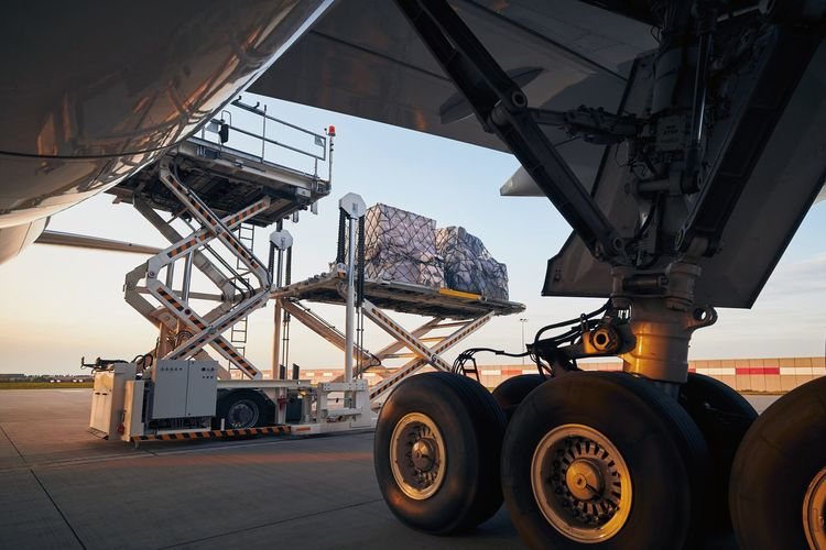 Loading of cargo containers to plane at airport. preparation freight airplane before flight.