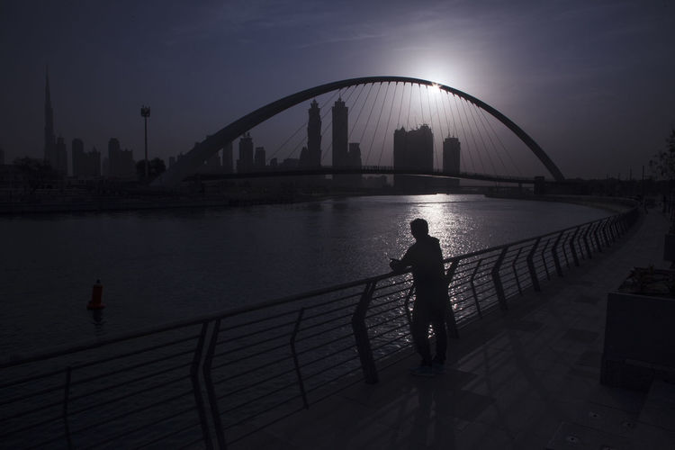 Architecture Bridge - Man Made Structure Building Exterior Built Structure City Cityscape Connection Dubai Canal Dubai Morning View Illuminated Lifestyles Men Nature Night One Person Outdoors Railing Real People River Silhouette Sky Standing Travel Destinations Waiting Water