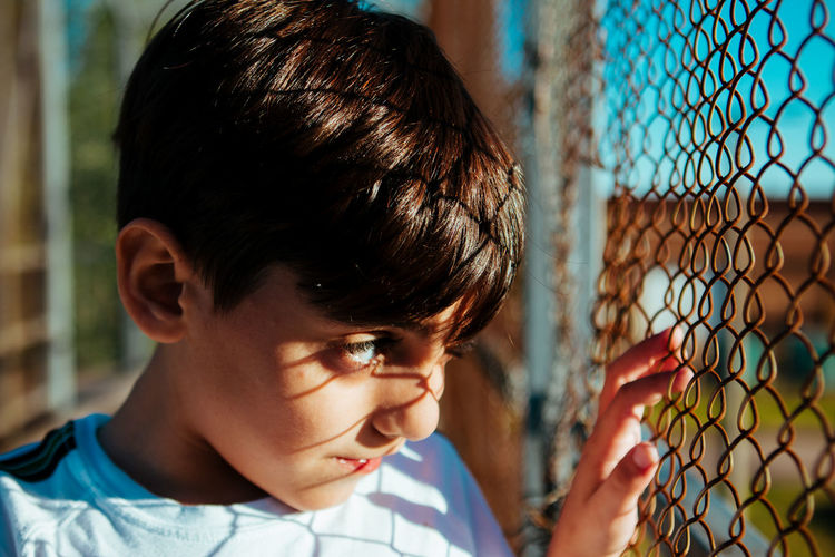 Close-up portrait of boy looking through fence